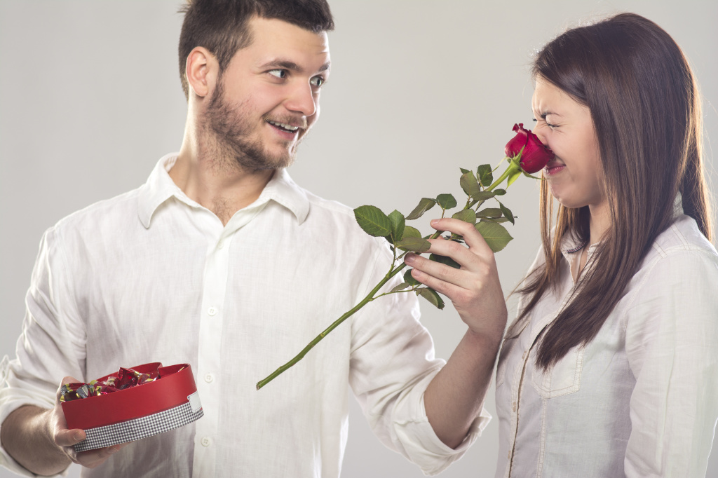 Young man putting rose on girlfriend's nose